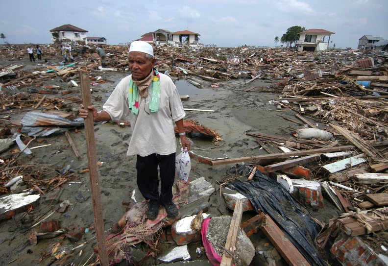 File photo of Acehnese man walking through debris left behind by last week's massive tsunami in the town of Banda Aceh